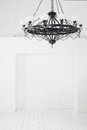 Vintage black chandelier with candles in an empty room white walls and floors Stock Images