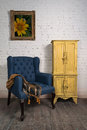 Vintage blue armchair, yellow cupboard and framed painting Royalty Free Stock Photo