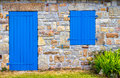 Vintage blue door and window on the facade of an old cottage stone wall. Royalty Free Stock Photo