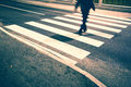 Vintage blurry pedestrian street crossing and grunge road with feet and grunge filter effect used Royalty Free Stock Image