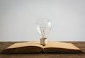 Vintage book and light bulb on wood table Stock Photos