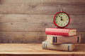 Vintage books and clock on wooden table with copy space