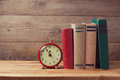 Vintage books and clock on wooden table Royalty Free Stock Photo
