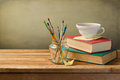 Vintage books cup of tea and painting brushes on wooden table Royalty Free Stock Image