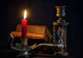 Vintage books in dark room candlestick with red candle and hourglass Royalty Free Stock Photography
