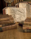 Vintage books old maps on a wooden table Royalty Free Stock Photo