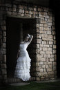 Vintage bride leaning against brick wall Stock Photos