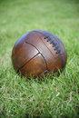 Vintage brown football soccer ball green grass field sits in Royalty Free Stock Photos