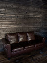 Vintage brown leather sofa on a wooden wall and floor Royalty Free Stock Photo
