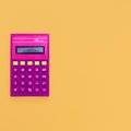 Vintage calculator on bright yellow background Royalty Free Stock Photo