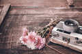 Vintage camera with bouquet of flowers on old wood background Royalty Free Stock Photo