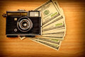 Vintage camera money wooden background Royalty Free Stock Images
