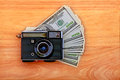 Vintage camera money wooden background Stock Photo