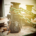 Vintage camera near a mooring bollard on pier Royalty Free Stock Image