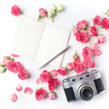 Vintage camera pink roses and note on white background. Flat lay. Top view Royalty Free Stock Photo