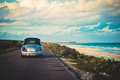Vintage car driving by the beach Royalty Free Stock Photo