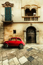 Vintage car old italian scene an small red parked in front of a historical house with windows and balcony stone retro floor Royalty Free Stock Photo