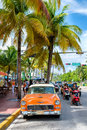 Vintage car and people at Ocean Drive, a popular destination in Royalty Free Stock Photo