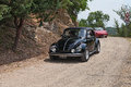 Vintage car volkswagen beetle type runs on a dirt road in the italian hills during the rally raduno auto e moto d epoca on july in Royalty Free Stock Photo