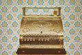 Vintage cash register in front of retro wallpaper Royalty Free Stock Photo