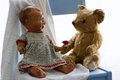 Vintage ceramic doll antique teddy and fresh red rose seemingly offering a to a bear on a white blanket on a blue chair white Stock Photography