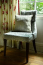 Vintage chair with pillow a beside the window Stock Photos