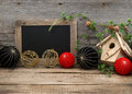 Vintage christmas decoration with blackboard for your text over rustic wooden background red and black china style balls and Royalty Free Stock Image