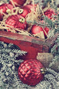 Vintage christmas ornaments glass packed in an old antique wooden box with snow covered pine boughs surrounding them extreme Stock Photos