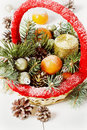 Vintage christmas or xmas composition basket with tangerines pine cone golden balls fir branches and candle toning new year Royalty Free Stock Photos