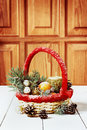 Vintage christmas or xmas composition. basket with tangerines, pine cone, golden balls, fir branches and candle Royalty Free Stock Photo
