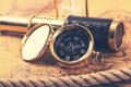 Vintage compass and telescope on ancient world map Royalty Free Stock Photo