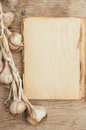 Vintage cookbook blank and organic garlic on wooden background Royalty Free Stock Photography