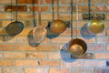 Vintage copper utensils hand crafted antique hang in front of rustic red brick wall in country kitchen Stock Photography