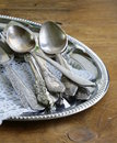 Vintage cutlery with old fashioned napkin on a silver tray Stock Image