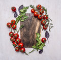 Vintage cutting board with herbs and vegetables on wooden rustic background top view close up place text,frame