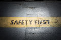 Vintage dark tone of Safety first sign on yellow line at metal Royalty Free Stock Photo