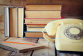 Vintage dial phone, phone book next to stack of old books over wooden table. vintage filtered image Royalty Free Stock Photo