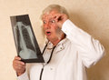 Vintage doctor with x ray examining an and looking surprised Royalty Free Stock Images