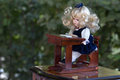 Vintage doll baby in school uniform seated at desk sold on flea market in slovenia Royalty Free Stock Photo