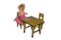 Vintage doll isolated on white background sitting at the table Royalty Free Stock Images