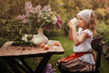 Vintage dressed child girl on garden tea party in spring Royalty Free Stock Photo