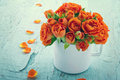 Vintage edited orange roses in a white cup on blue shabby chic wooden background Royalty Free Stock Photos