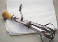 Vintage egg beater a sitting on a white napkin on a table Royalty Free Stock Image