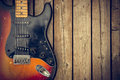 Vintage electric guitar background a beat up and dirty body against a natural wood grain boards Stock Images