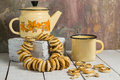 Vintage enamelware and a bunch of small dry bagels yellow teapot cup with poppy seeds on white wooden table on background Stock Photos