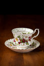Vintage English fine bone china teacups,  Christmas Rose pattern, on antique walnut table, isolated in dark background Royalty Free Stock Photo