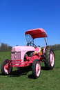 Vintage farm tractor pink parked in green farmland in spring on blue sky background Stock Images