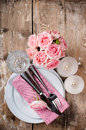 Vintage festive table setting with pink roses candles and cutlery on an old wooden board Stock Photo