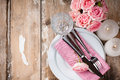 Vintage festive table setting with pink roses candles and cutlery on an old wooden board Royalty Free Stock Image