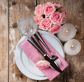 Vintage festive table setting with pink roses candles and cutlery on an old wooden board Royalty Free Stock Photo